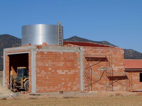 depósito de agua de chapa galvanizada sobre estructura de obra almacén