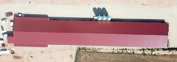 Vista panoramica de una nave de pollos con depósito de agua, estercolero, fosa para bajas y tanque de gas. Vista aérea del terreno que ocupa la instalación ganadera para cria de pollos.